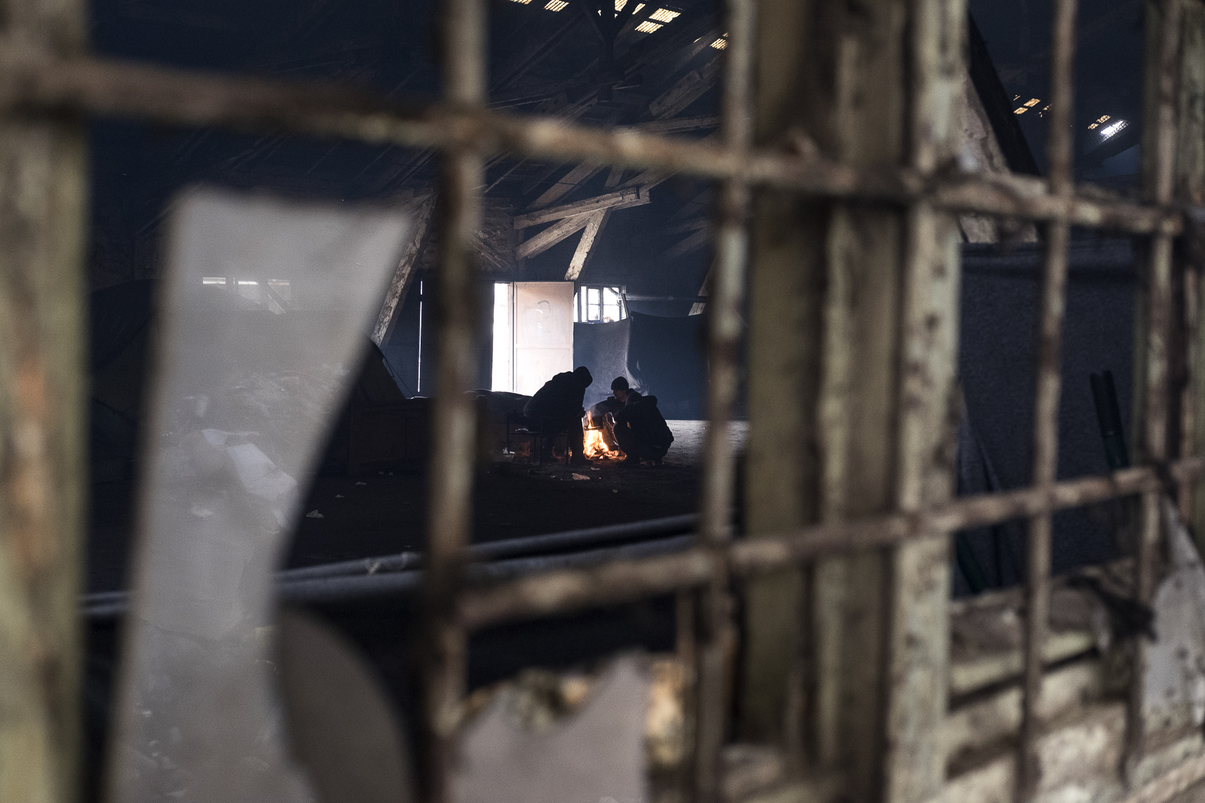 Seen through the window of an abandoned warehouse where they took shelter in Belgrade, Serbia, migrants warm themselves around a fire. February 11, 2107.