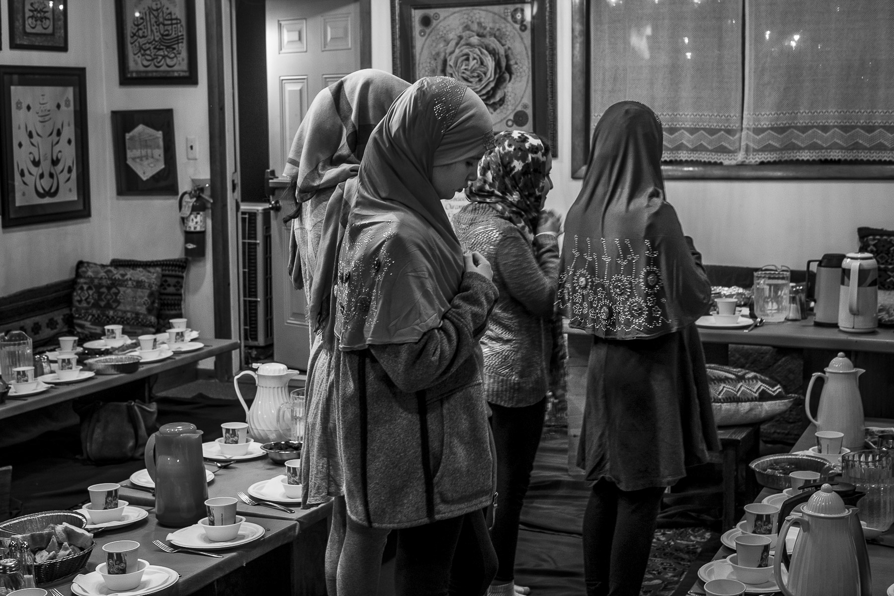 Young girls make their sunset prayer in the dining area of the mosque. Often, there are too many people to fit into the common prayer room and many members find themselves praying in between the tables that have been set for dinner.