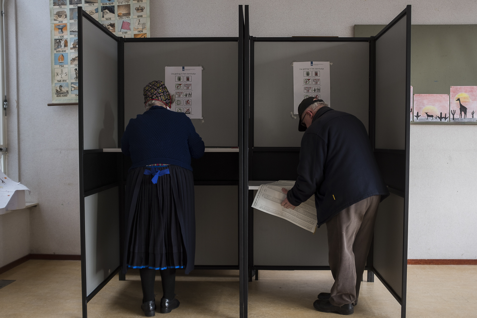 An elderly couple cast their ballots for the Dutch general elections at a polling station set up in a school in Staphorst, Netherlands, Wednesday, March 15, 2017.