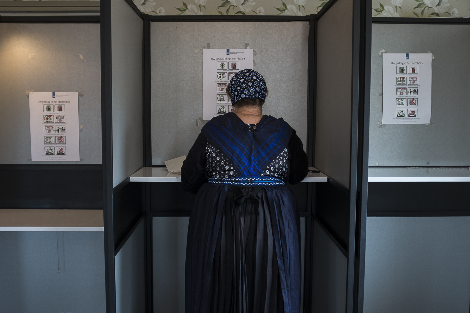 An elderly woman dressed in the traditional clothing of the town casts her ballot for the Dutch general elections at a polling station set up in a cafe in Staphorst, Netherlands, Wednesday, March 15, 2017.