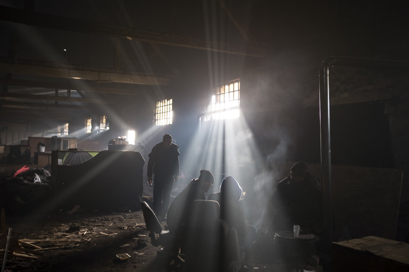 Migrants chat while warming themselves around a fire inside an abandoned warehouse where they took shelter in Belgrade, Serbia. February 14, 2107.