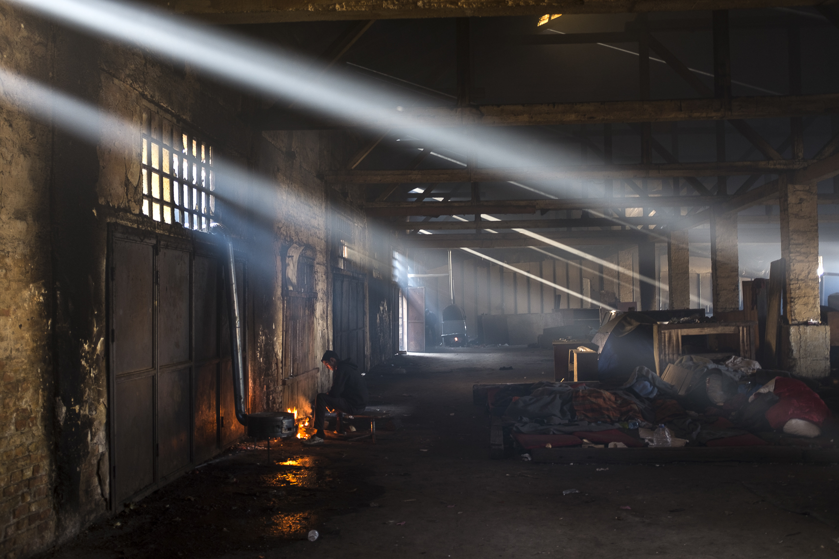 A migrant makes tea on a fire inside an abandoned warehouse where he and others took shelter in Belgrade, Serbia. February 12, 2107.