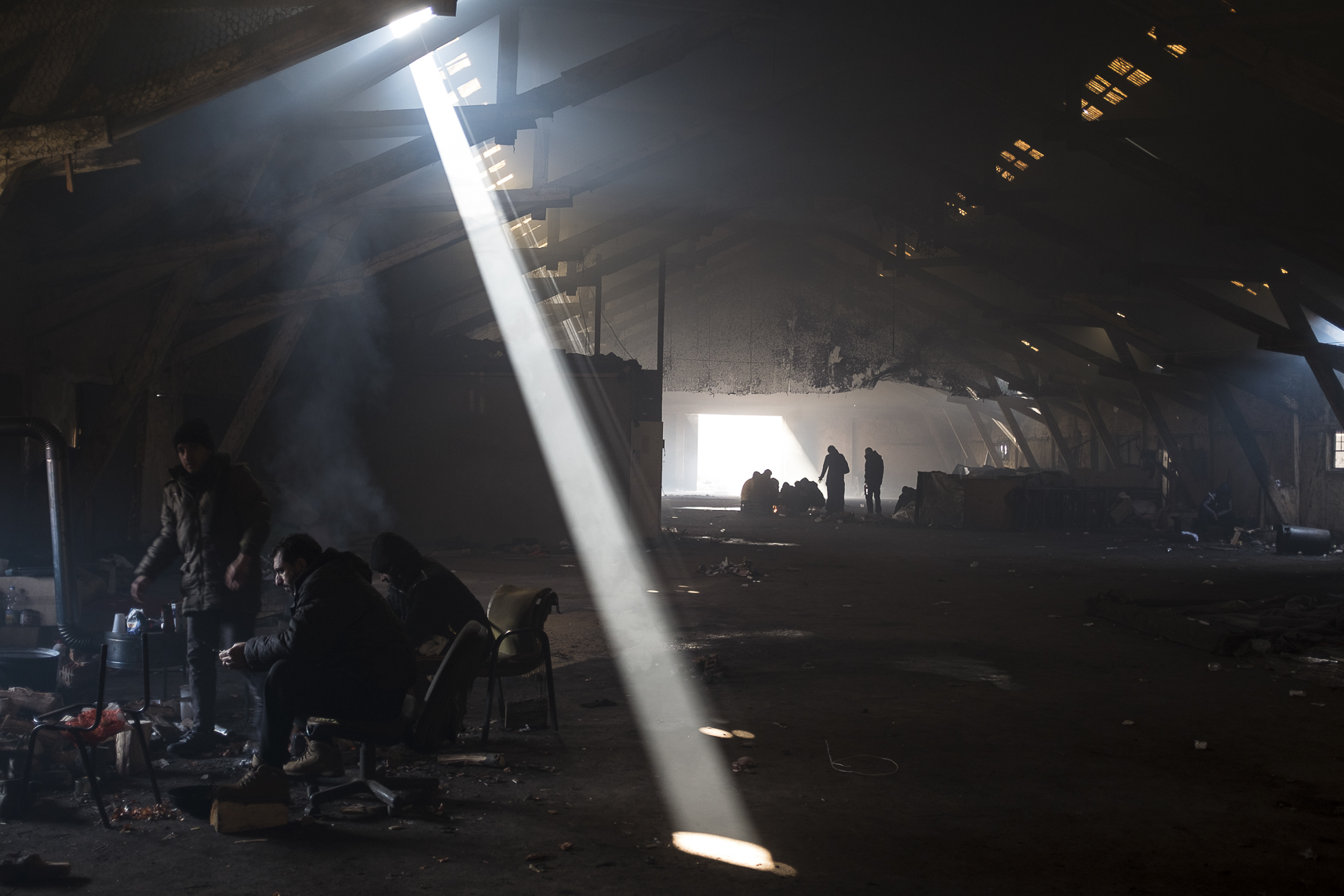 Migrants shield themselves from the cold around a fire inside an abandoned warehouse where they took shelter in Belgrade, Serbia. February 15, 2107.