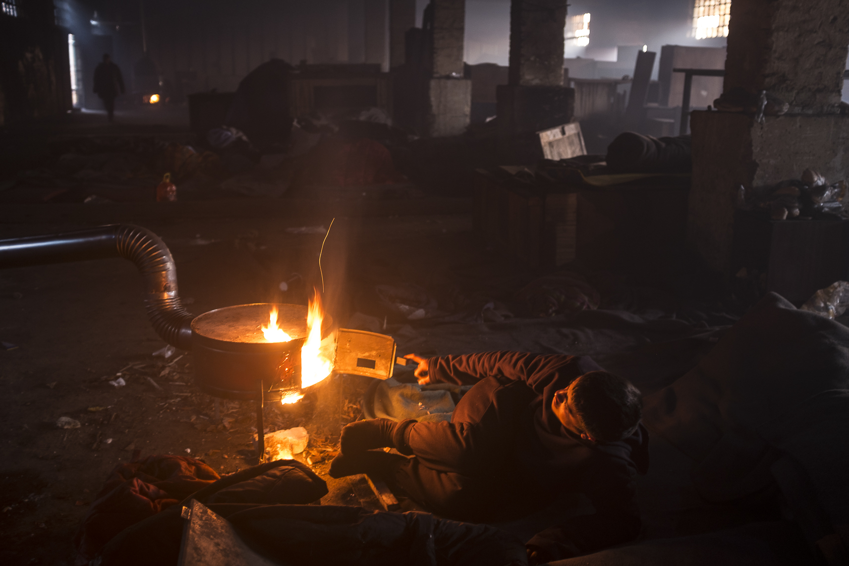 A young migrant lies on the ground next to a fire inside an abandoned warehouse where he and others took shelter in Belgrade, Serbia. February 12, 2107.