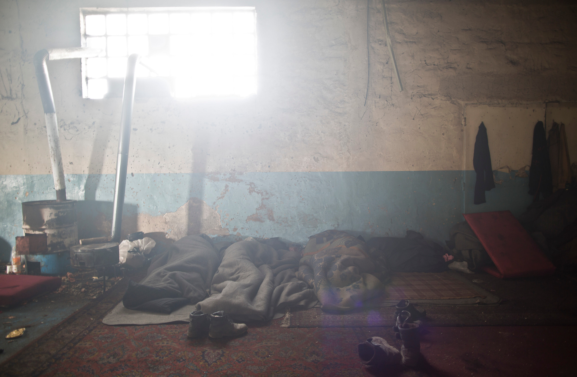 A group of migrants sleep on the ground of an abandoned warehouse where they took shelter in Belgrade, Serbia. February 16, 2107.