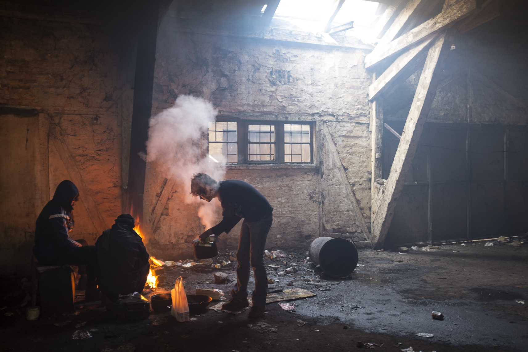 Migrants cook lunch on a fire inside an abandoned warehouse where they took shelter in Belgrade, Serbia. February 15, 2107.
