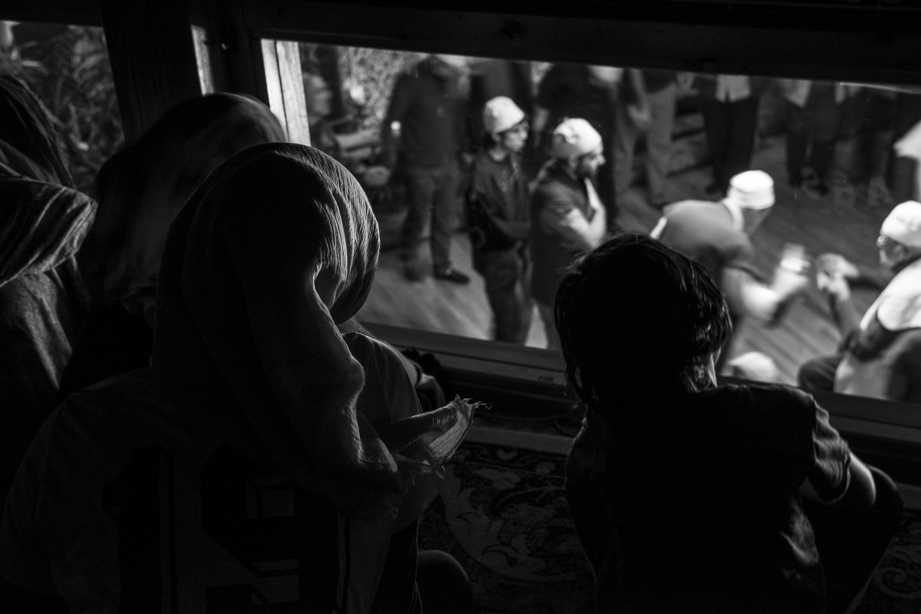 Young teenage girls watch the Zikr—a Sufi ceremony honoring Allah—through the upstairs window in the children's section of the mosque. Parents are required to keep their young children and babies with them during the Zikr, but teenagers are allowed to watch from above, with permission from their parents.