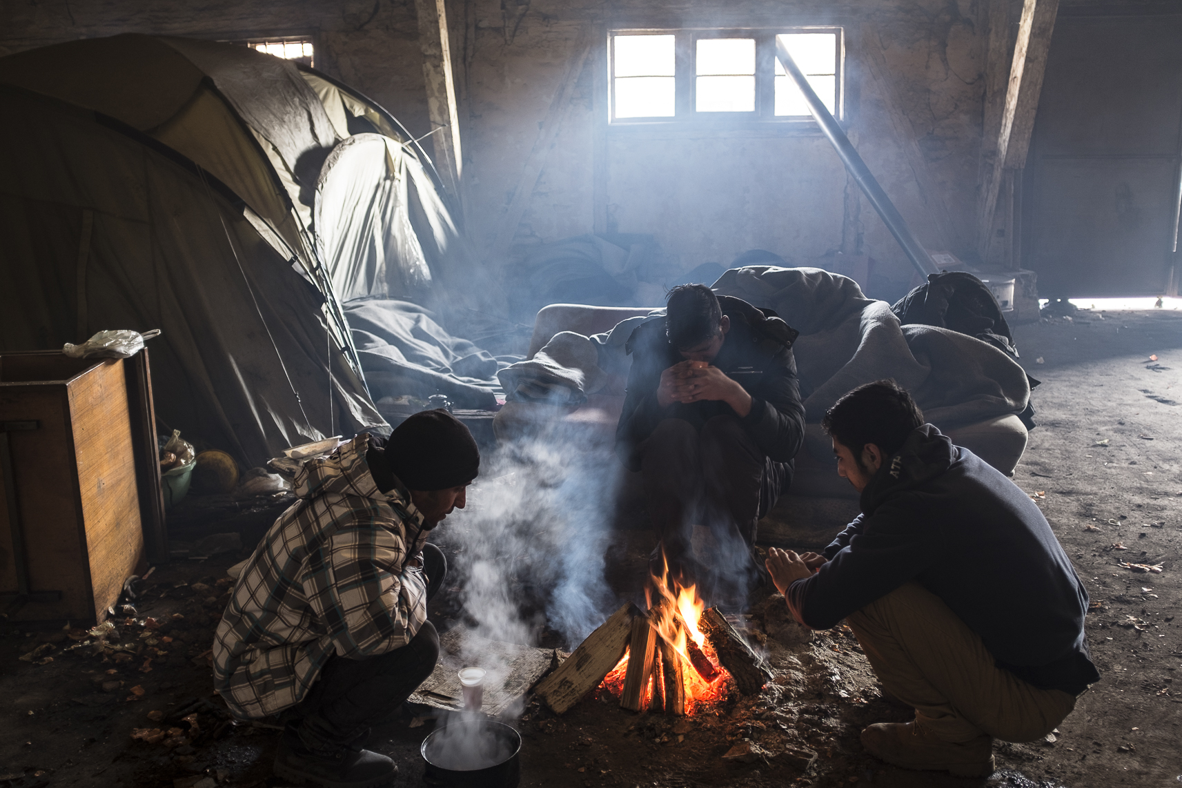 Migrants drink tea while sitting around a fire warming themselves inside an abandoned warehouse where they took shelter in Belgrade, Serbia. February 14, 2107.