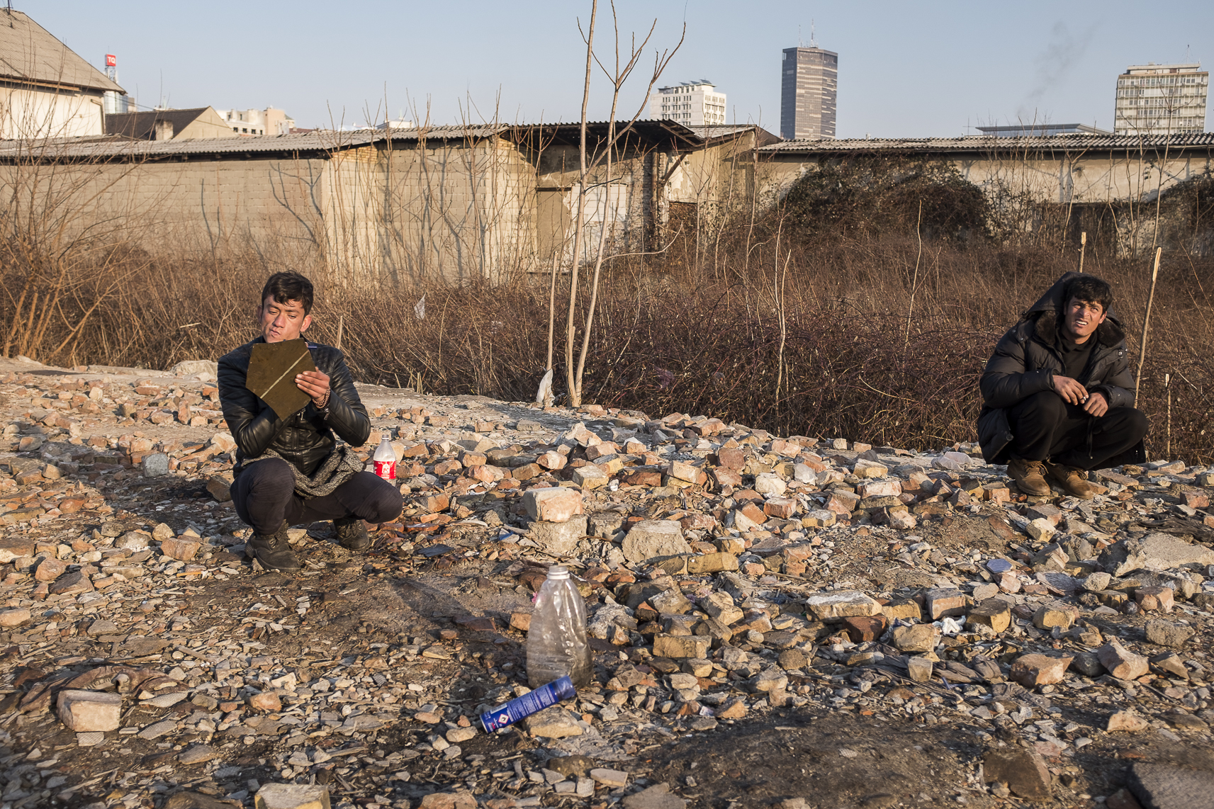 A migrant, left, shaves outside an abandoned warehouse where he and others took shelter in Belgrade, Serbia. February 13, 2107.