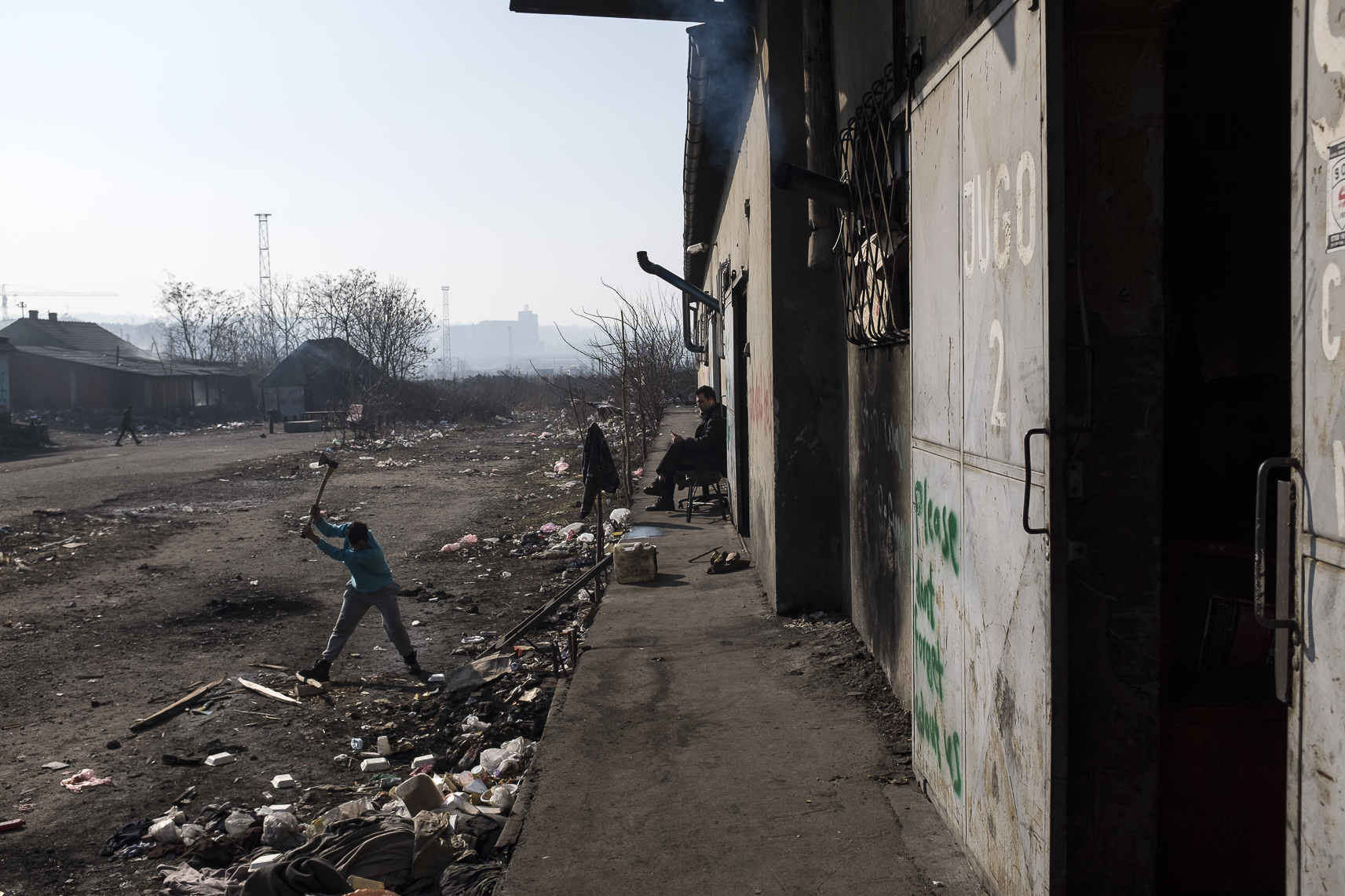 A migrants chops wood while another talks on the phone outside an abandoned warehouse where they took shelter in Belgrade, Serbia. February 15, 2107.