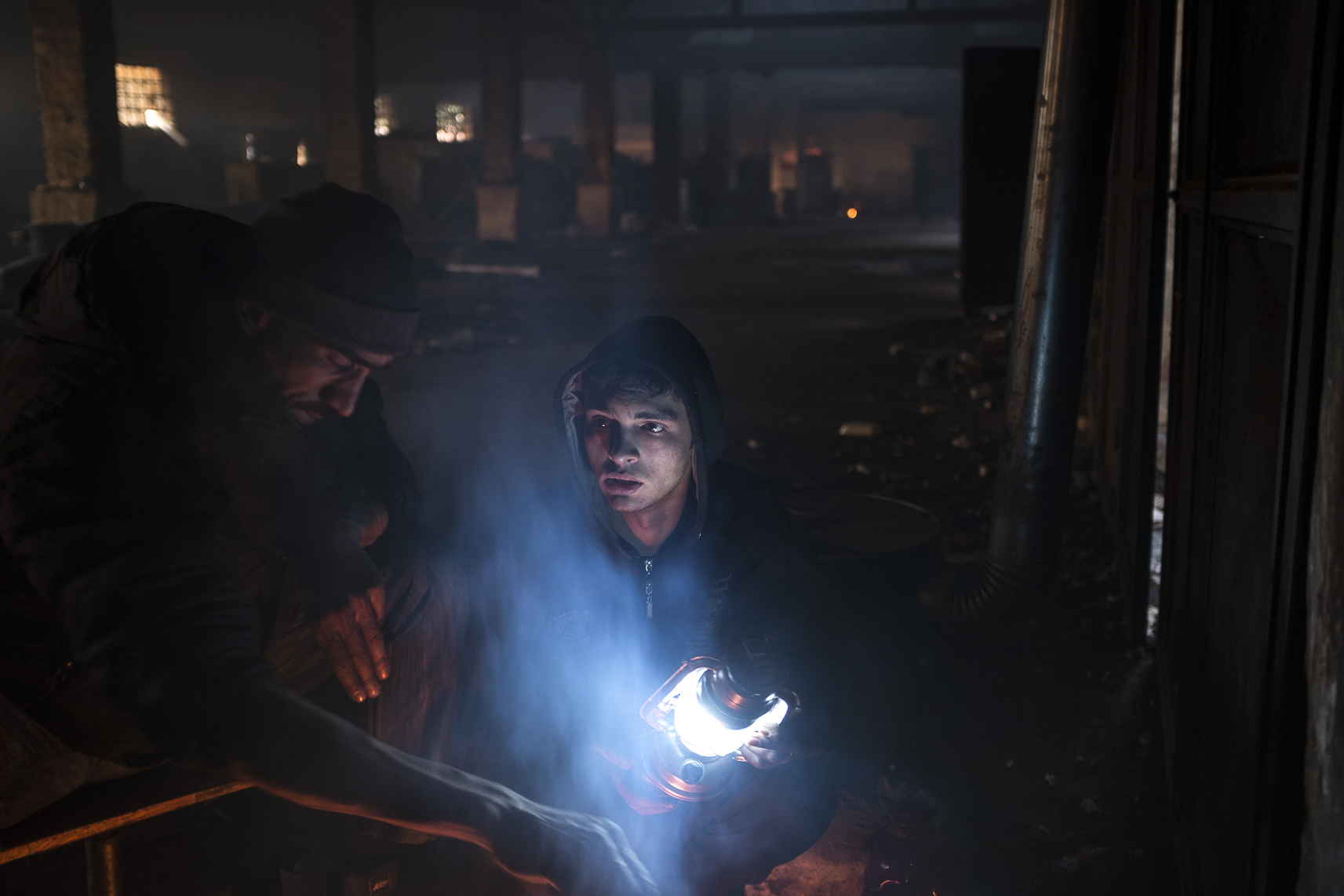 A migrant holds a light near a fire he and others warm themselves around inside an abandoned warehouse where they took shelter in Belgrade, Serbia. February 13, 2107.