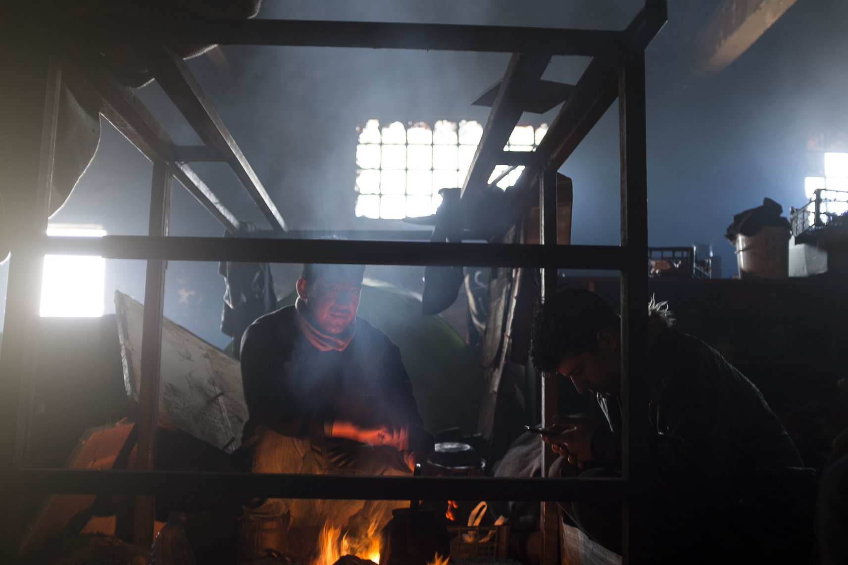 A migrant looks on while he and another cook lunch inside an abandoned warehouse where they took shelter in Belgrade, Serbia. February 15, 2107.