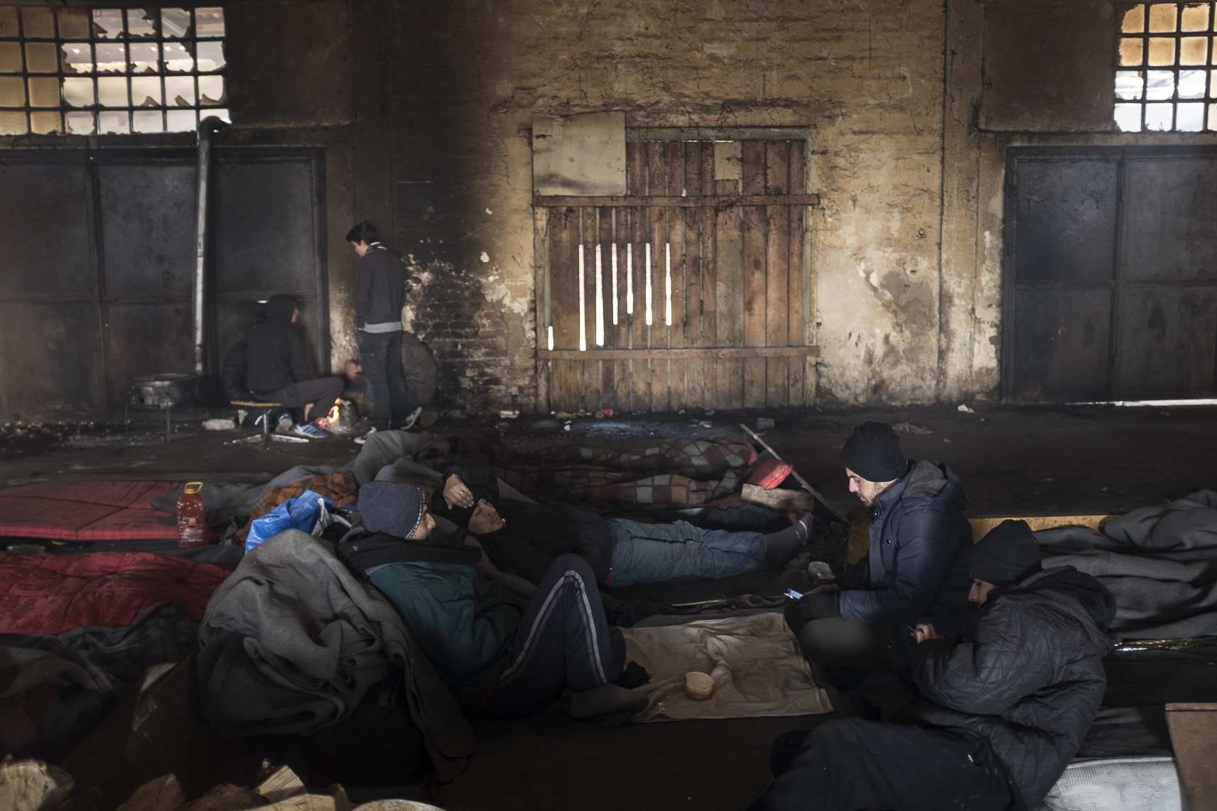 Migrants rest on the ground inside an abandoned warehouse where they took shelter in Belgrade, Serbia. February 13, 2107.