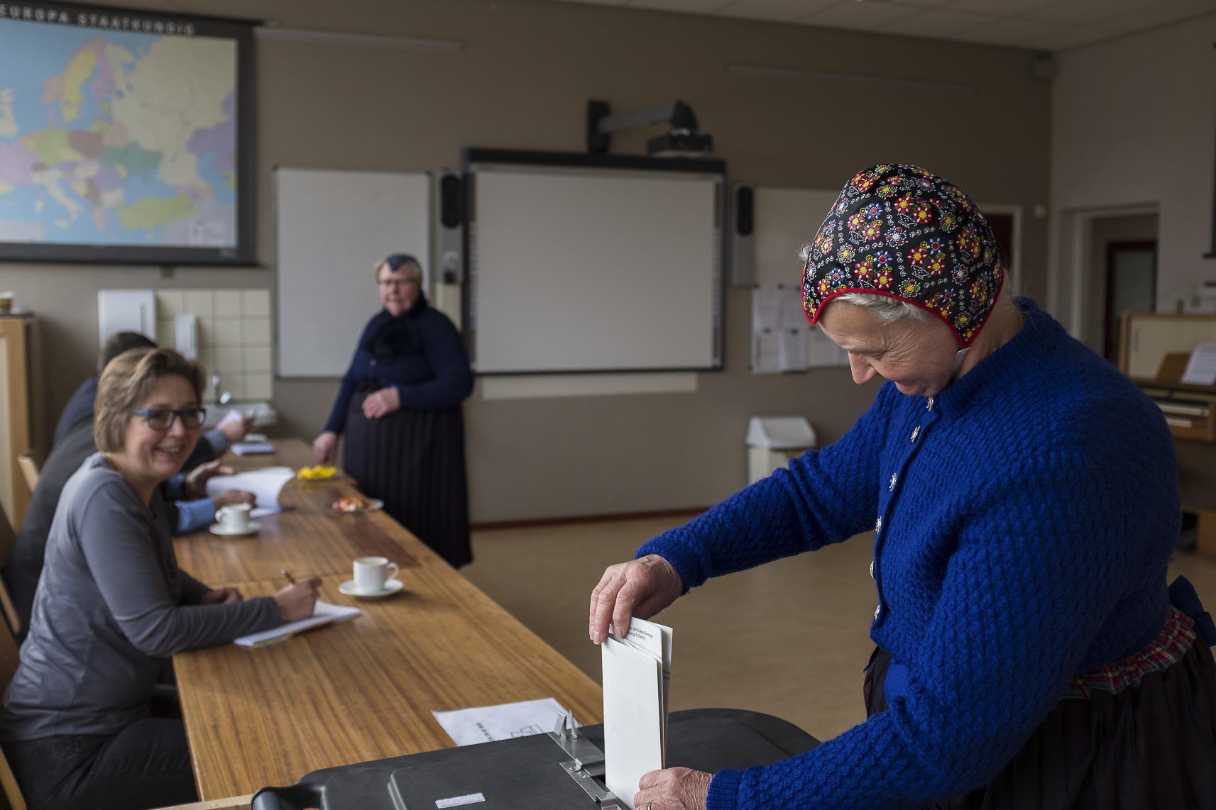 An elderly woman dressed in the traditional clothing of the town casts her ballot for the Dutch general elections at a polling station set up in a school in Staphorst, Netherlands, Wednesday, March 15, 2017.