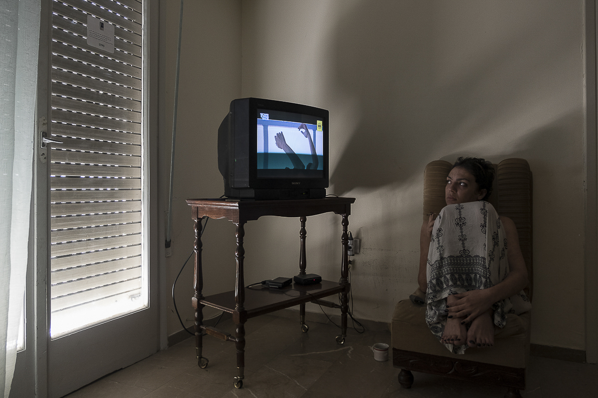 Yasmin, 24, a transgender woman from Morocco watches TV while relaxing at her apartment in Athens, Greece | July 13, 2017