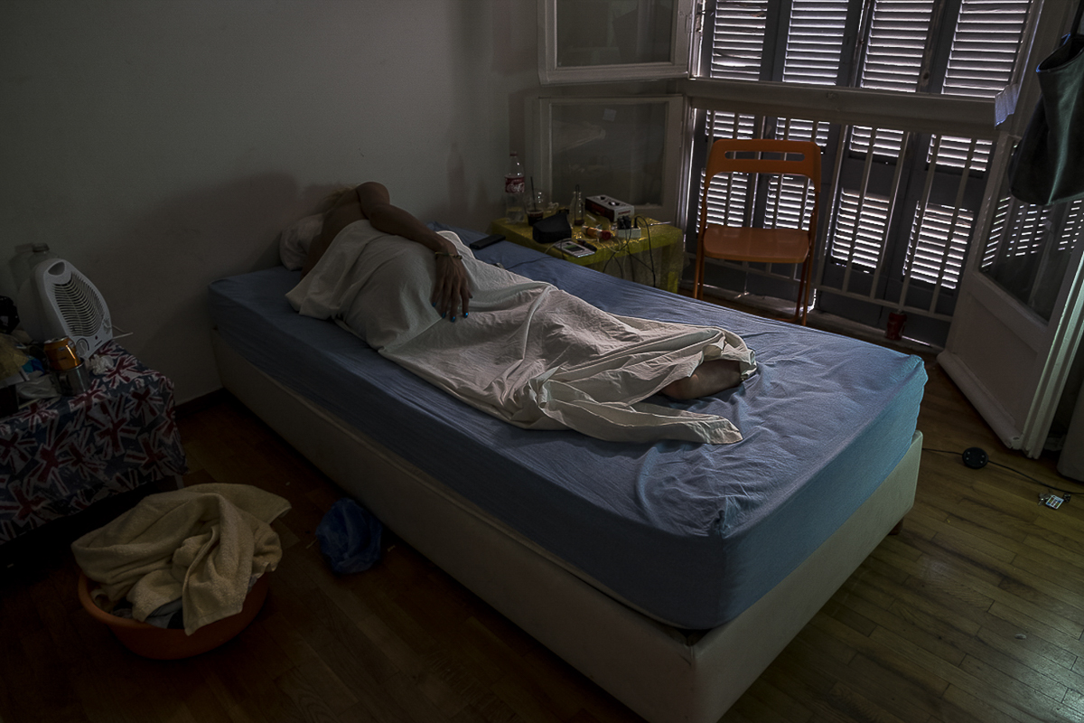 Maya, a transgender woman from Tunisia, takes a nap at her apartment in Athens, Greece | September 4, 2017