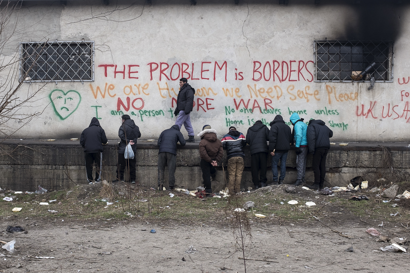 Migrants eat their lunch donated by volunteers outside an abandoned warehouse where they took shelter in Belgrade, Serbia. February 14, 2107.