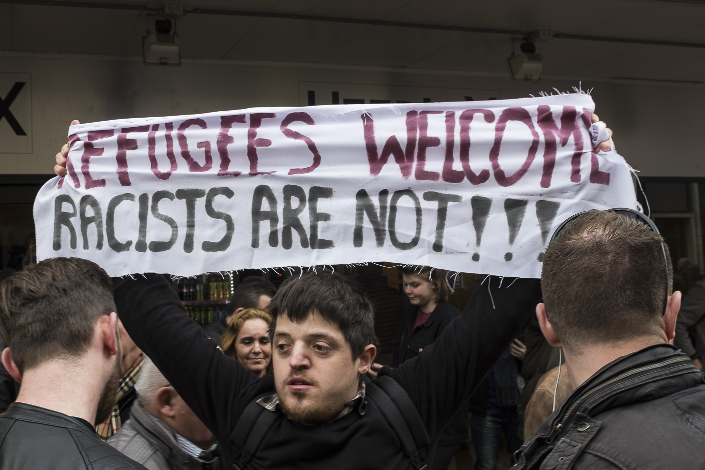 """A protester holds a sign, Refugees Welcome Racists Are Not"""" during a campaign rally for firebrand anti-Islam lawmaker Geert Wilders during the Dutch general elections in Heerlen, Netherlands, on March 11, 2017."""