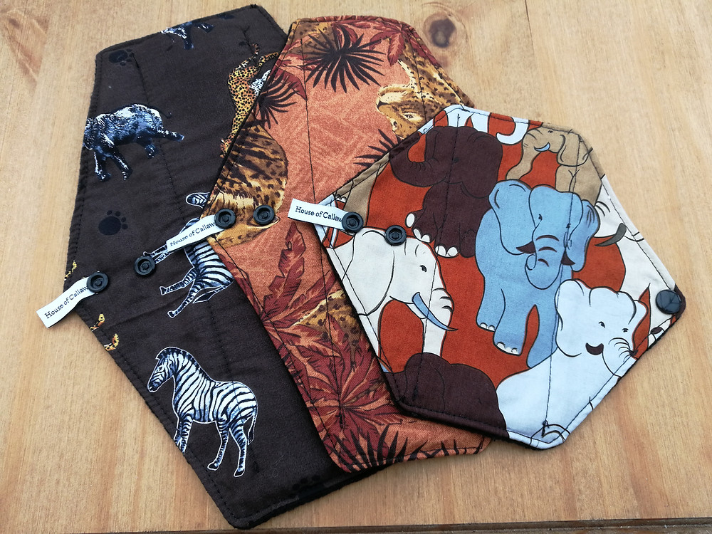 three pads laid on a table, right: brown pad with safari animal print, middle: orange pad with leopard design, right, orange pad with coloured elephants (brown, white, blue and beige)