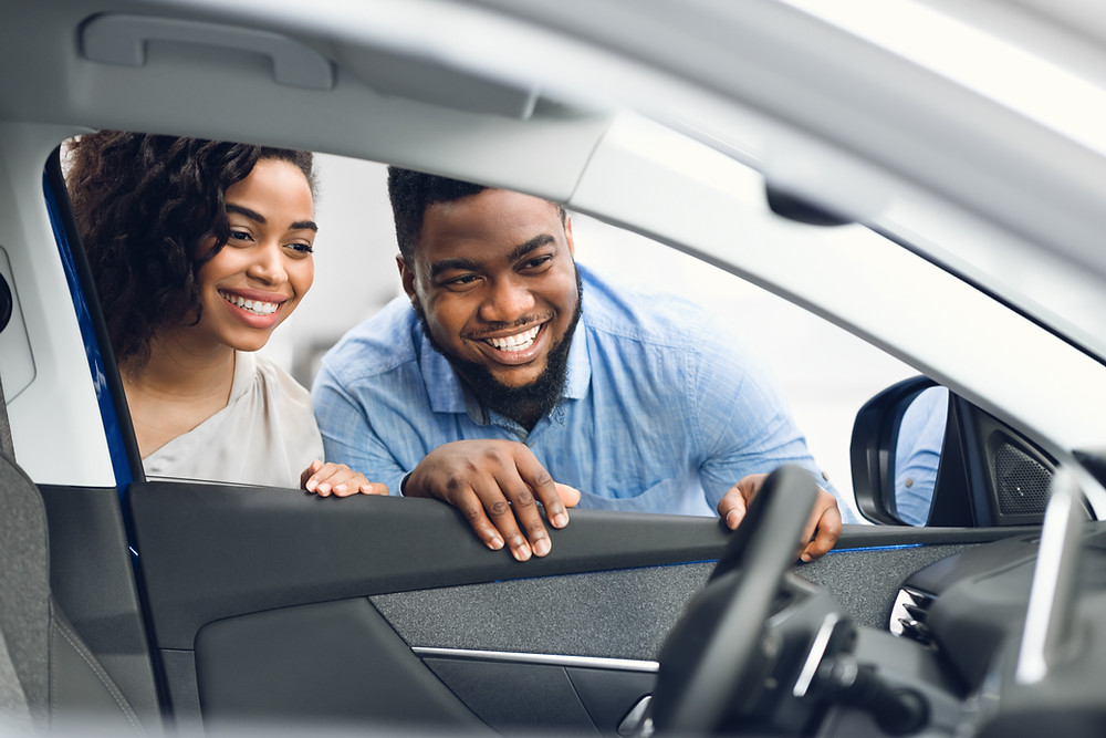a young couple smiling looking inside the driver's side window of a new vehicle