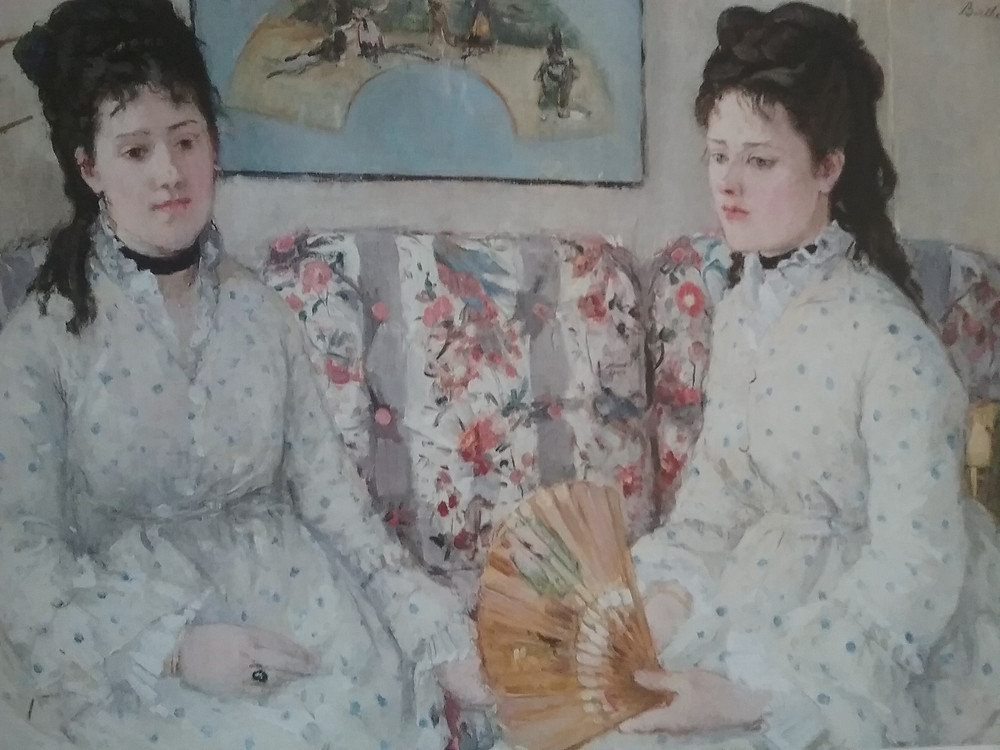Two young 19th century upper class women on a sofa.