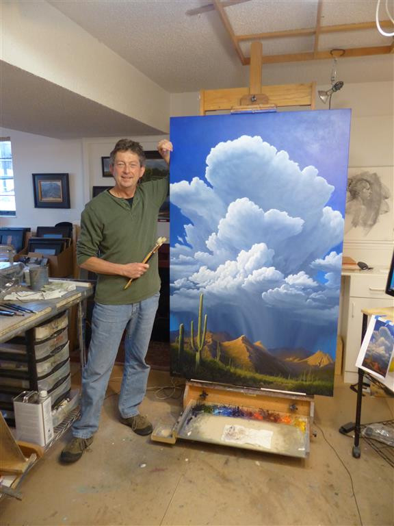 Artist stands beside a large painting of clouds over a southwestern landscape.