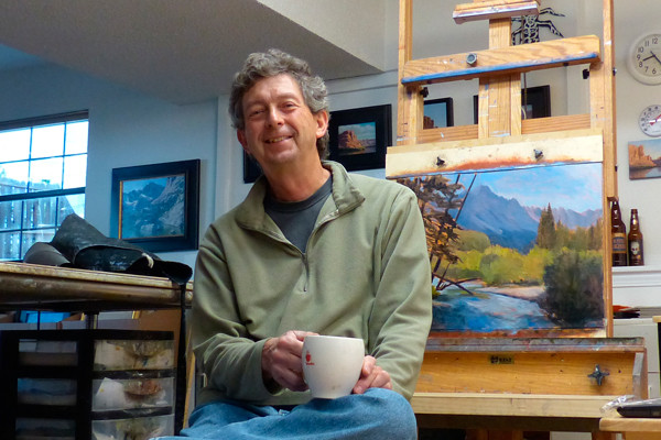 Artist in his studio with painting on an easel.