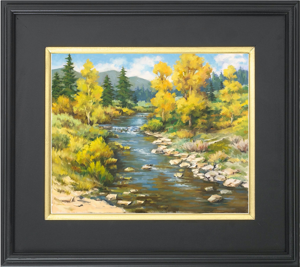 Golden trees in a mountain landscape with stream