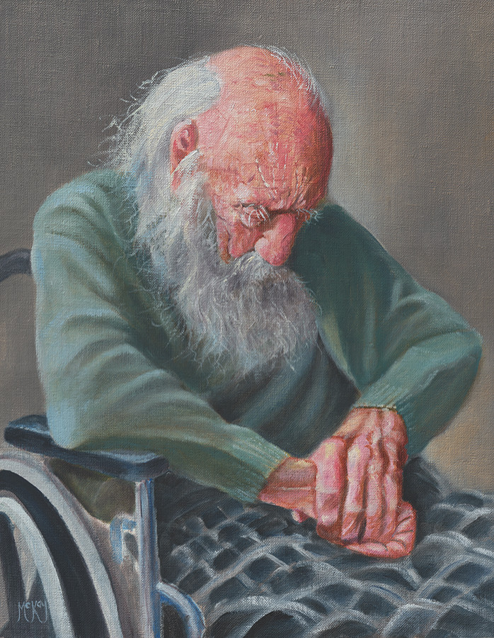 An elder bearded man sits asleep in a wheel chair.