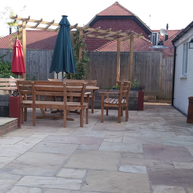 Indian sandstone patio with steps and oak sleepers