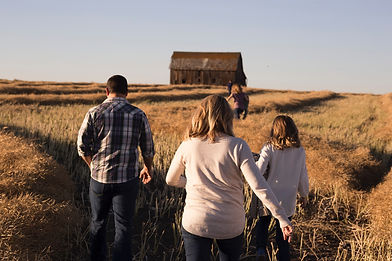 Family out in a open field by a barn