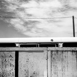 White bus peeking over white fence