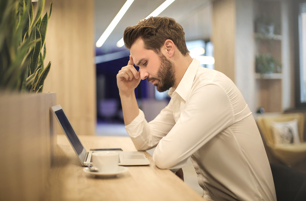 Frustrated man at desk with laptop and coffee