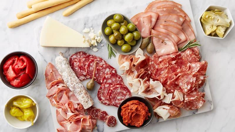 Italian charcuterie board - prosciutto, salami, mortadella, olive, cheese, breadsticks, peppers
