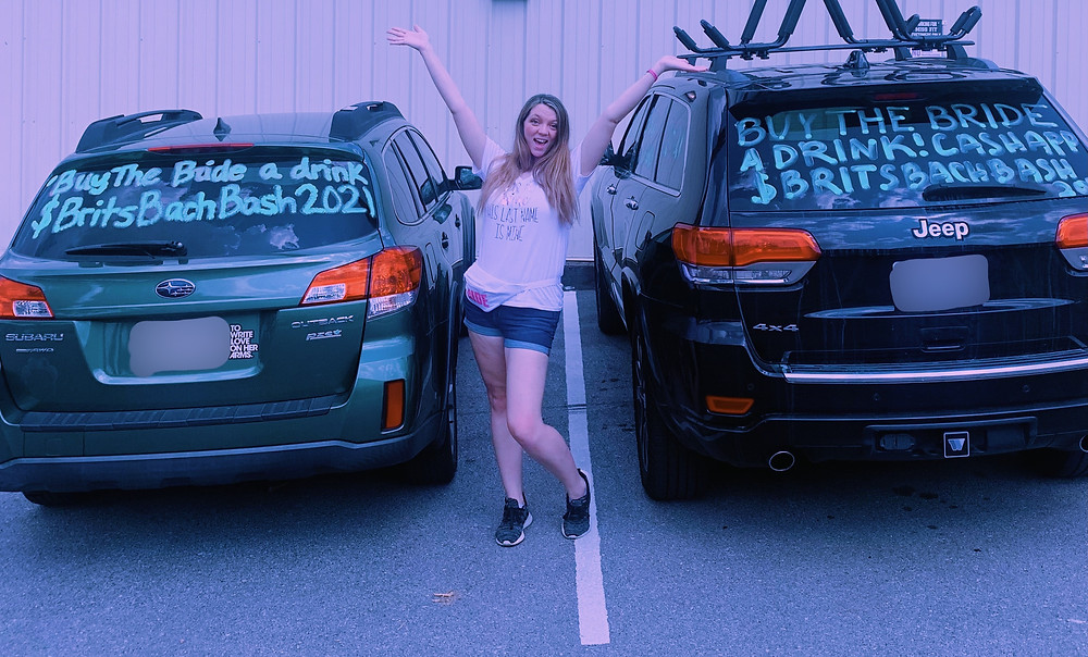 Woman excitedly standing between two cars
