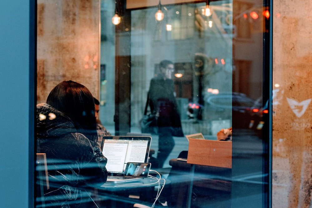 Woman in cafe on laptop and Facetime.