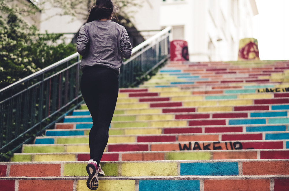 Women running up colorful steps post-baby run