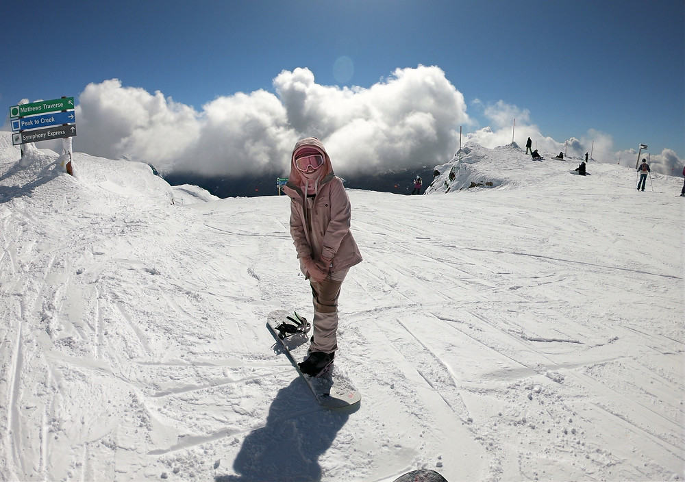 Pink female snowboarder, on the peak of Whistler Mountains, with clouds above her head