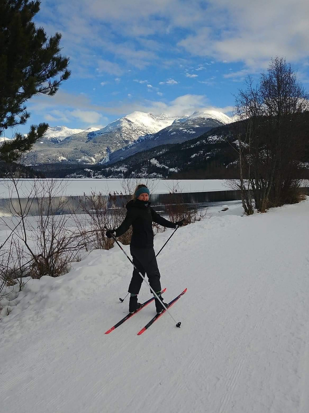 Girl, wearing cross-country skis, with beautiful mountain backdrop and blue skies
