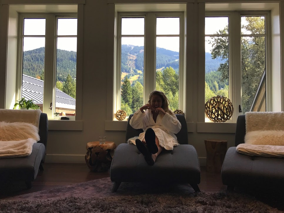Girl in robe, sitting in lounge chair, with beautiful mountain backdrop