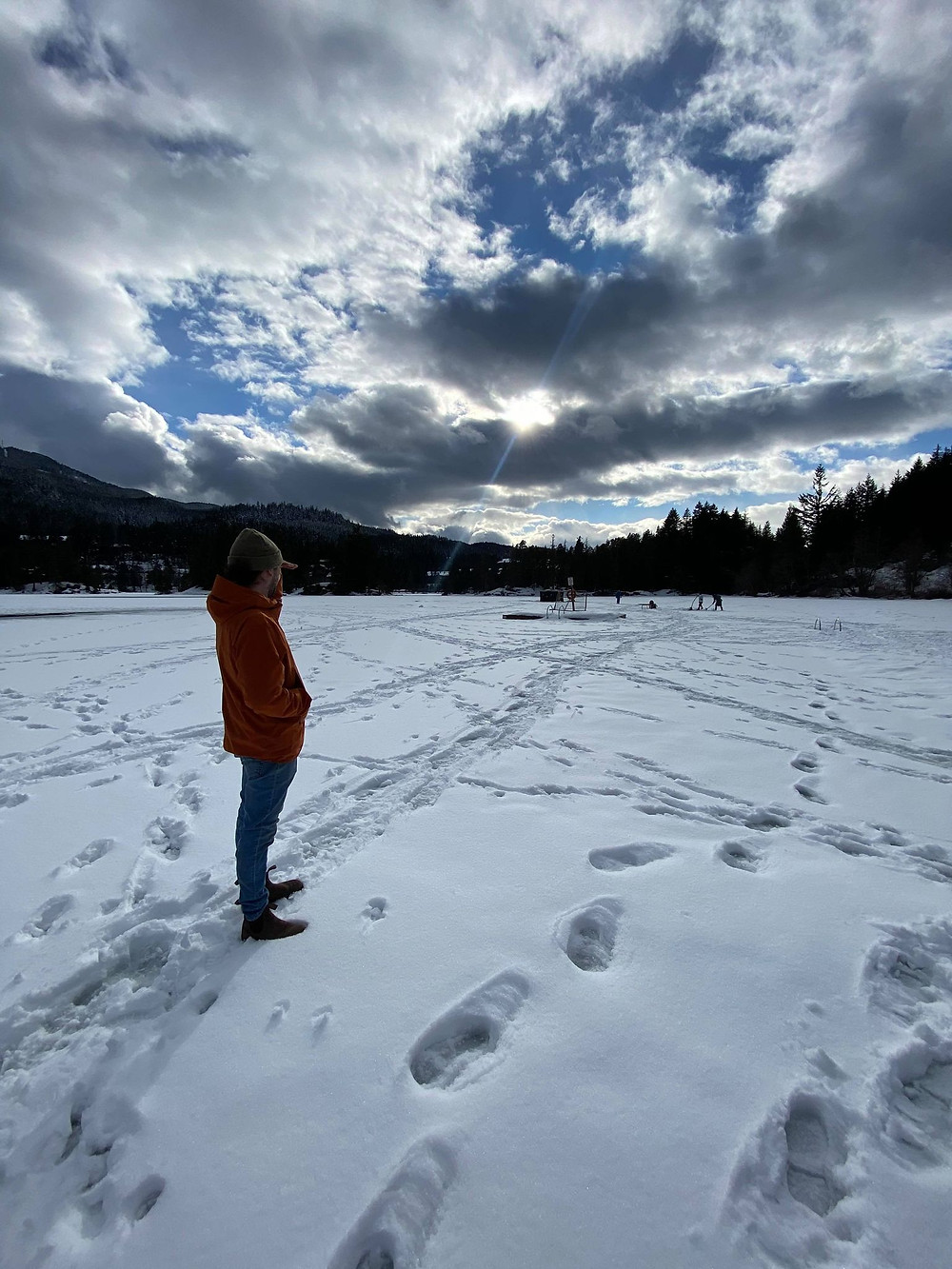 Boy, standing on frozen lake, clouds above and blue sky