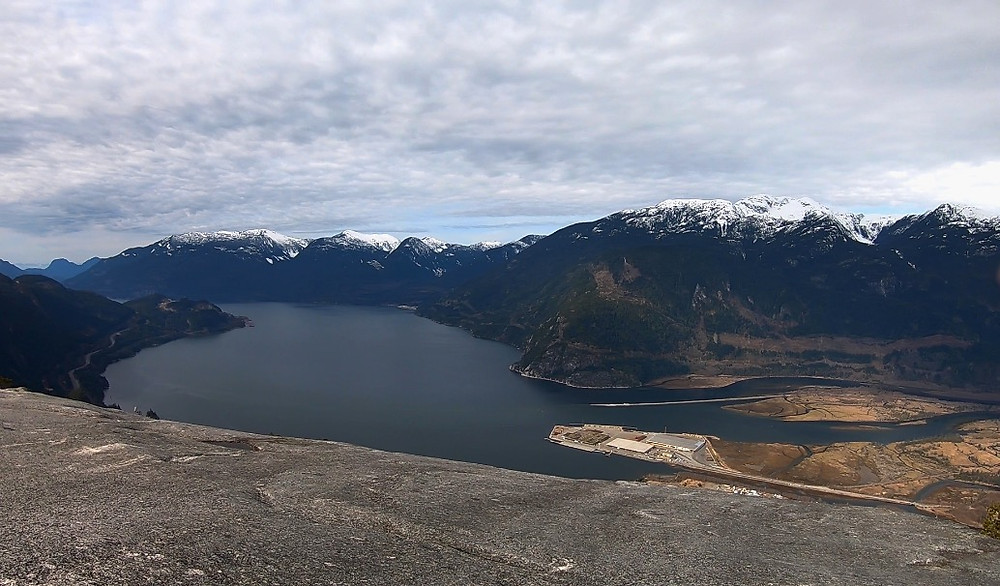 Top of Stawamus Chief, with mountains surrounding the ocean, above the clouds