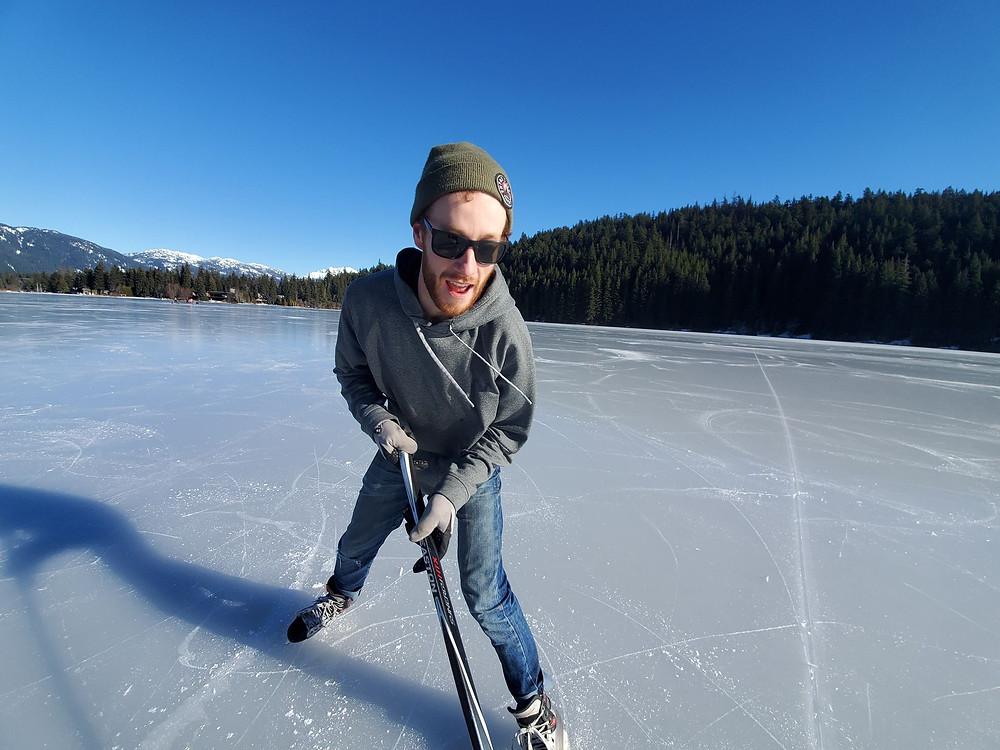 Boy, playing hockey on lake, blue sky, beautiful day
