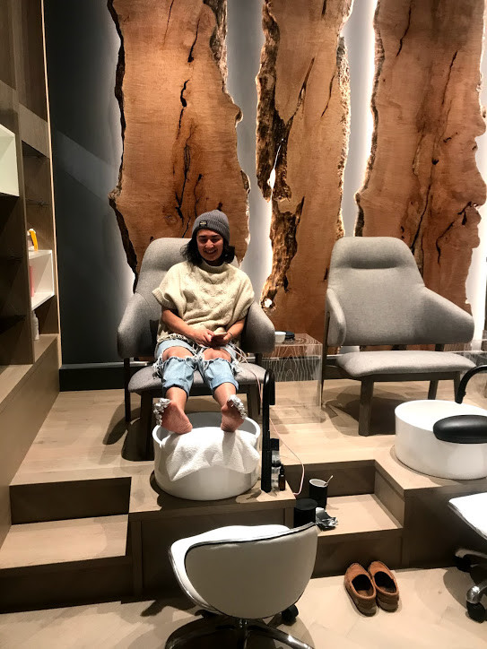 A girl, sitting in comfty pedicure station, with gorgeous wood carvings behind her