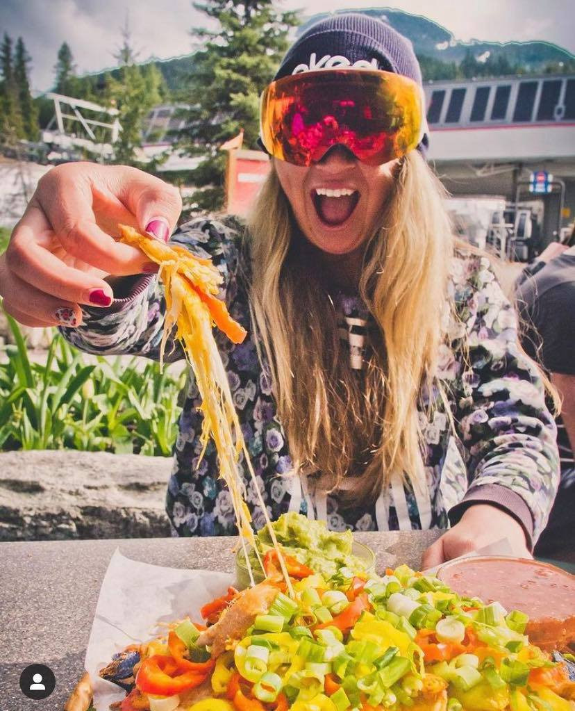 girl, with nachos and snowboard goggles, enjoying apres ski