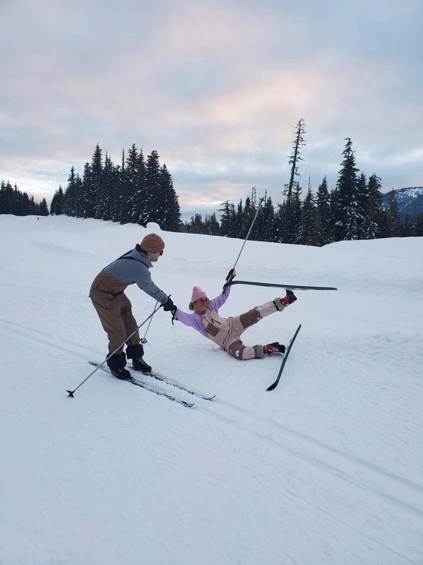 Boy helping girl, girl fell with skis, beautiful sky at Callaghan