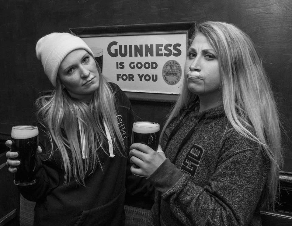 """two girls, enjoying a pint of Guinness, with sign behind """"Guinness is good for you"""""""