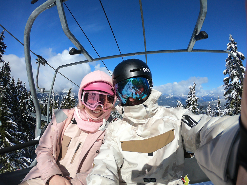 Girl and boy, on chairlift Garbanzo, surrounded by trees, mountains and blue sky