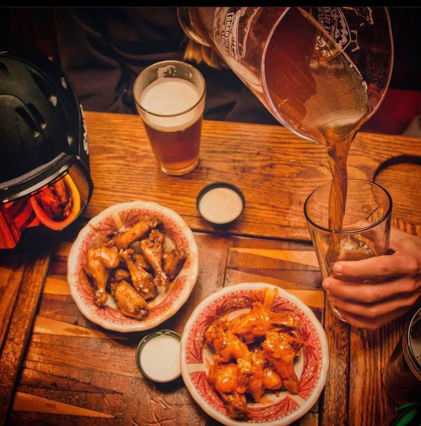 Pouring jug of beer, two pounds of wings and dipping sauces, apres ski
