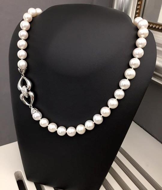 Collana di perle naturali coltivate in diametro mm 10,5 con chiusura in oro bianco 18kt con interni alla chiusura diamanti taglio brillante color G ct 0,75. Collana infilata a nodi